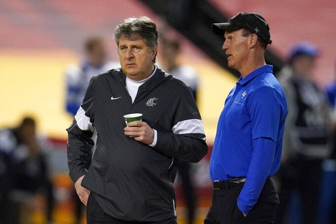 Washington State coach Mike Leach, left, and Air Force  coach Troy Calhoun talk before the Cheez-It Bowl NCAA college football bowl game, Friday, Dec. 27, 2019, in Phoenix. (AP Photo/Rick Scuteri)