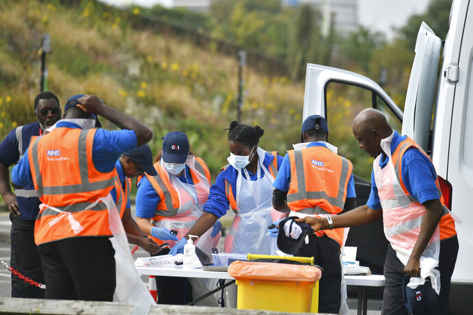 Workers prepare ahead of opening at a Coronavirus testing centre in Southwark, south London, Wednesday, Sept. 16, 2020. The British government plans to ration coronavirus testing, giving priority to health workers and care home staff after widespread reports that people throughout the country were unable to schedule tests. Prime Minister Boris Johnson on Wednesday will face questions about his handling of the COVID-19 pandemic in the House of Commons and before a key committee amid the outcry over the shortage of testing. (Dominic Lipinski/PA via AP)