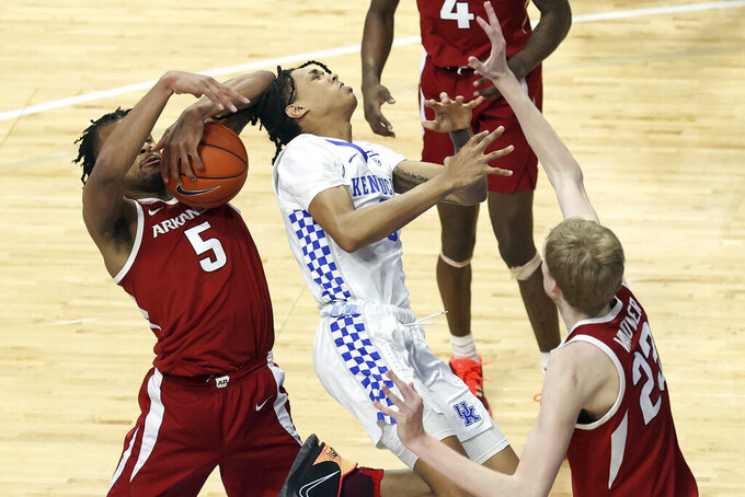 Kentucky's B.J. Boston, middle, has the ball taken from him by Arkansas' Moses Moody (5) near Connor Vanover during the second half of an NCAA college basketball game in Lexington, Ky., Tuesday, Feb. 9, 2021. (AP Photo/James Crisp)