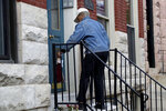 Sarah Holley delivers a package to the doorstep to the home of U.S. Rep. Elijah Cummings, D-Md., Thursday, Oct. 17, 2019, in Baltimore. Cummings, a sharecropper's son who rose to become the powerful chairman of one of the U.S. House committees leading an impeachment inquiry of President Donald Trump, died Thursday, Oct. 17, 2019, of complications from longstanding health issues. He was 68. (AP Photo/Julio Cortez)