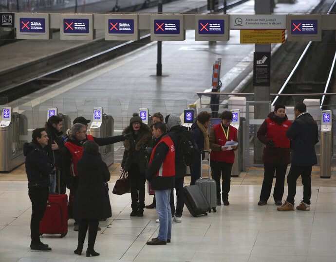 Railway employees, with red jackets, give informations to travellers at the Gare de Lyon train station, Friday, Dec. 6, 2019 in Paris. Frustrated travelers are meeting transportation chaos around France for a second day, as unions dig in for what they hope is a protracted strike against government plans to redesign the national retirement system. (AP Photo/Rafael Yaghobzadeh)