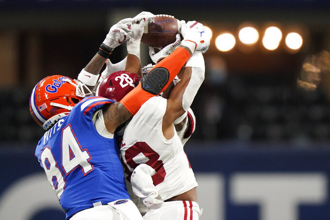 Florida tight end Kyle Pitts (84) misses the catch against Alabama defensive back Josh Jobe (28) during the second half of the Southeastern Conference championship NCAA college football game, Saturday, Dec. 19, 2020, in Atlanta. (AP Photo/Brynn Anderson)