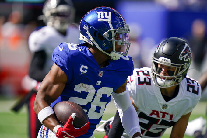 New York Giants running back Saquon Barkley (26) runs the ball past Atlanta Falcons free safety Erik Harris (23) during the first half of an NFL football game, Sunday, Sept. 26, 2021, in East Rutherford, N.J. (AP Photo/Seth Wenig)
