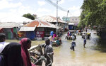 In this image made from video, residents move through floodwaters on foot and using donkey carts in Afgoye, Somalia Sunday, Aug. 9, 2020. Severe flooding continues to displace thousands of people in Somalia and the government in recent days has issued new warnings to communities living along the Jubba and Shabelle rivers. (AP Photo)