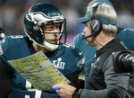 "FILE - In this Feb. 4, 2018, file photo, Philadelphia Eagles head coach Doug Pederson, right, talks to Nick Foles during the first half of the NFL Super Bowl 52 football game against the New England Patriots, in Minneapolis. Facing the mighty New England Patriots on the NFL's biggest stage, Philadelphia Eagles coach Doug Pederson's decision to try a trick play _ the ""Philly Special"" _ on a fourth down late in the first half of Super Bowl 52 will be remembered as one of the gutsiest calls in sports history. That signature moment between Foles and Pederson standing on the sideline discussing the play was turned into a bronze statue that sits outside the team's stadium as a reminder of the greatest play in franchise history. (AP Photo/Matt York, File)"