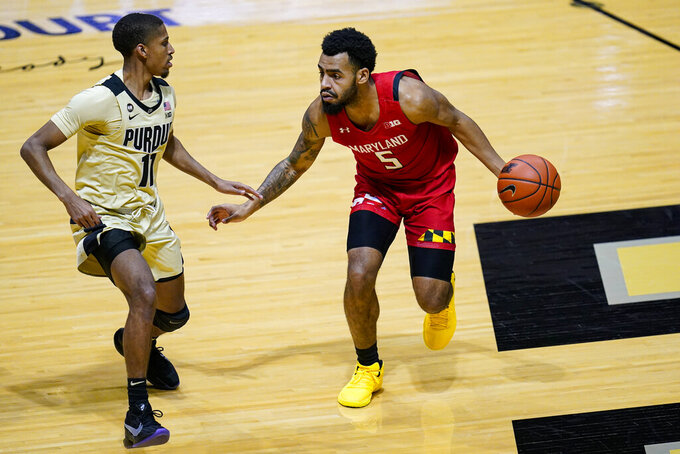 Maryland guard Eric Ayala (5) drives on Purdue guard Isaiah Thompson (11) during the first half of an NCAA college basketball game in West Lafayette, Ind., Friday, Dec. 25, 2020. (AP Photo/Michael Conroy)