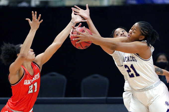 Stephen F. Austin forward Aiyana Johnson, right, pulls in the rebound from Sam Houston State forward Madelyn Batista, left, in front of Avery Brittingham, back, during the first half of an NCAA college basketball game for the Southland Conference women's tournament championship Sunday, March 14, 2021, in Katy, Texas. (AP Photo/Michael Wyke)