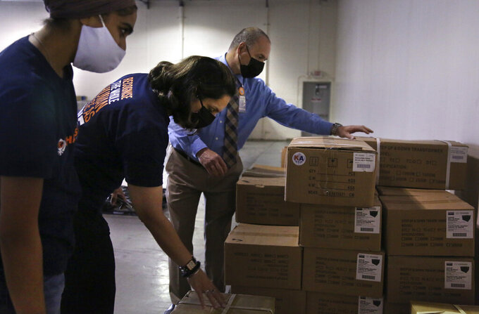 From left, Dr. Abhu Kaur, Manpreet Kaur, director for Khalsa Aid USA, and Ray Fredericks, assistant director for Medisys, sort and pack dozens of electrical transformers, which will be shipped to New Delhi with oxygen concentrators this week on New York's Long Island, Friday, May 7, 2021. With teams deployed in India to help support COVID-19 patients, Khalsa Aid USA plans to provide a total of 500 oxygen concentrators and 500 transformers to cities throughout the country. (AP Photo/Jessie Wardarski)