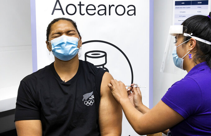 New Zealand olympian shot putter Dame Valerie Adams reacts as she receives her COVID-19 vaccination in Auckland, New Zealand, Monday, April 17, 2021. Some wealthy nations that were most praised last year for controlling the coronavirus are now lagging far behind in getting their people vaccinated — and some, especially in Asia, are seeing COVID-19 cases grow. (Brett Phibbs/New Zealand Herald via AP)