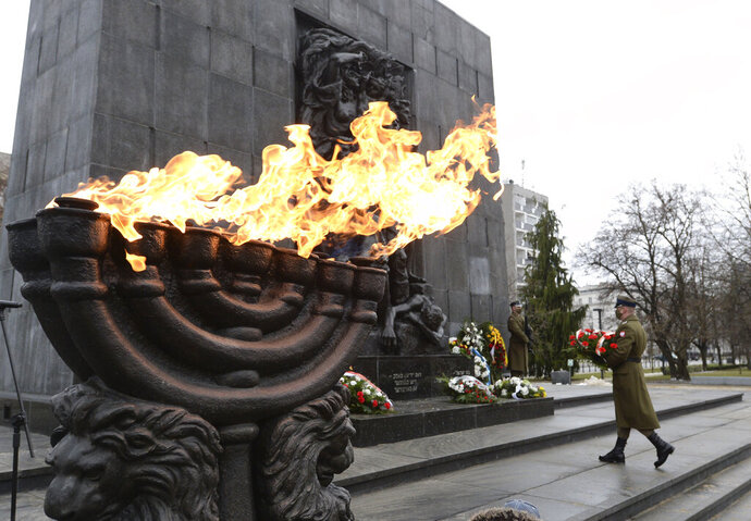 A wreath is laid at the monument to the Heroes of the Warsaw Ghetto in Warsaw, Poland, on Wednesday, Jan. 27, 2021, as part of world observances of the 76th anniversary of the liberation of the Nazi German death camp Auschwitz.  Some 1.1 million people, mostly Jewish, were killed during World War II. Most observances were held online, due to the coronavirus pandemic, and only few people attended the ceremony at the monument.(AP Photo/Czarek Sokolowski)