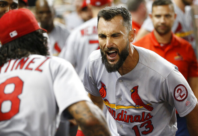 St. Louis Cardinals' Carlos Martinez, left, celebrates with Matt Carpenter (13), who hit a home run during the eighth inning of the team's baseball game against the Miami Marlins, Tuesday, Aug. 7, 2018, in Miami. Carpenter hit his 30th home run, a tiebreaking drive that lifted the Cardinals over the Marlins 3-2. (AP Photo/Wilfredo Lee)