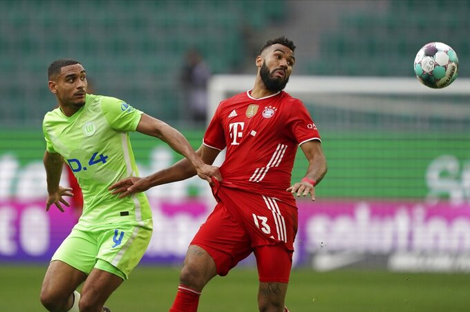 Bayern's Eric Maxim Choupo-Moting, right, and Wolfsburg's Maxence Lacroix challenge for the ball during the German Bundesliga soccer match between VfL Wolfsburg and FC Bayern Munich in Wolfsburg, Germany, Saturday, April 17, 2021. (AP Photo/Michael Sohn)