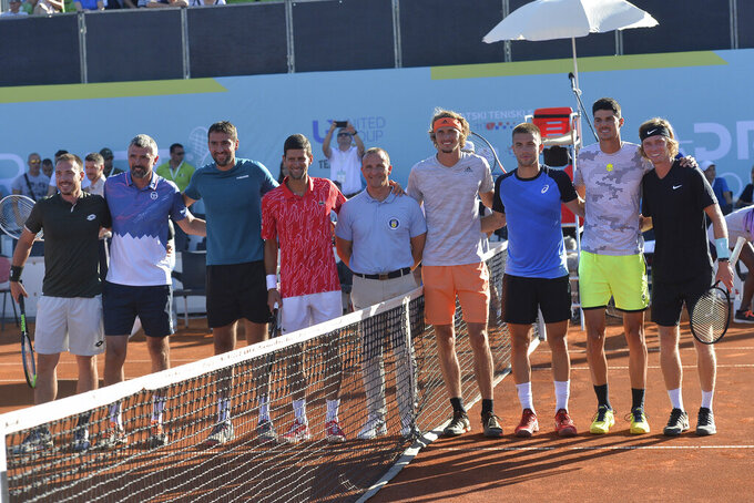 In this photo taken June 19, 2020, Serbian tennis player Novak Djokovic, fourth left, poses with other players at a tournament in Zadar, Croatia. Novak Djokovic has tested positive for the coronavirus after taking part in a tennis exhibition series he organized in Serbia and Croatia. (AP Photo/Zvonko Kucelin)