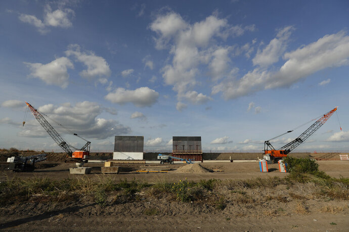 FILE - In this Nov. 7, 2019, file photo the first panels of levee border wall are seen at a construction site along the U.S.-Mexico border in Donna, Texas. Three years into Donald Trump's presidency, the U.S. government is finally ramping up its efforts to seize the private land it needs to build a border wall in South Texas. (AP Photo/Eric Gay, File)