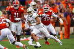Georgia Tech quarterback Jordan Yates (13) scrambles away from Clemson defenders Bryan Bresee (11) and Justin Foster (35) in the first half of an NCAA college football game Saturday, Sept. 18, 2021, in Clemson, S.C. (AP Photo/John Bazemore)