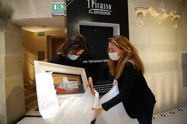 Raffle organizers Peri Cochin, left, and Arabenne Reille unbox the painting