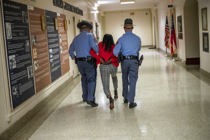 Rep. Park Cannon (D-Atlanta) is escorted out of the Georgia Capitol Building by Georgia State Troopers after being asked to stop knocking on a door that lead to Gov. Brian Kemp's office while Gov. Kemp was signing SB 202 behind closed doors at the Georgia State Capitol Building in Atlanta, Thursday, March 25, 2021. (Alyssa Pointer/Atlanta Journal-Constitution via AP)