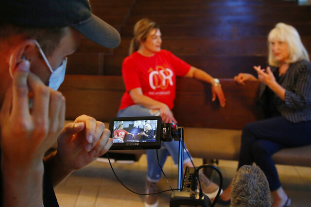 Teresa Stanfield, seated at center, the Oklahoma field director with Virginia-based Prison Fellowship, and Teresa Peden, right, pastor of recovery ministry at Crossing Community Church, are pictured in the camera display of videographer Drew Darby, left, Tuesday, Aug. 11, 2020, in Oklahoma City. Normally, Stanfield is behind bars, talking with inmates about how she changed the course of her troubled life. The coronavirus has forced her out of prisons. For the time being, Stanfield is videotaping her message. (AP Photo/Sue Ogrocki)