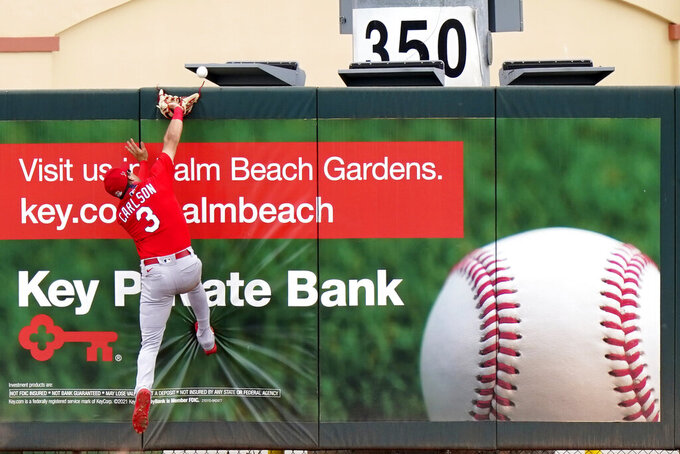St. Louis Cardinals left fielder Dylan Carlson (3) cannot get to a ball hit by Miami Marlins' Peyton Burdick for a solo home run during the fifth inning of a spring training baseball game, Monday, March 22, 2021, in Jupiter, Fla. (AP Photo/Lynne Sladky)
