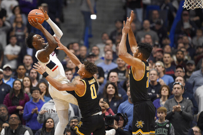 Connecticut's Sidney Wilson, left, shoots over Wichita State's Dexter Dennis, center, and Wichita State's Jaime Echenique, right, in the second half of an NCAA college basketball game, Sunday, Jan. 12, 2020, in Hartford, Conn. (AP Photo/Jessica Hill)