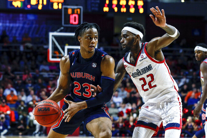 Auburn forward Isaac Okoro (23) drives to the basket as South Alabama guard Andre Fox (22) defends during the second half of an NCAA college basketball game, Tuesday, Nov. 12, 2019, in Mobile, Ala. Auburn won 70-69. (AP Photo/Butch Dill)