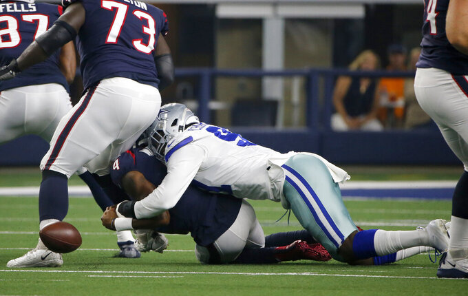 Houston Texans quarterback Deshaun Watson (4) fumbles the ball after being tackled by Dallas Cowboys' Taco Charlton (97) in the first half of a preseason NFL football game in Arlington, Texas, Saturday, Aug. 24, 2019. The Cowboys recovered the fumble. (AP Photo/Michael Ainsworth)