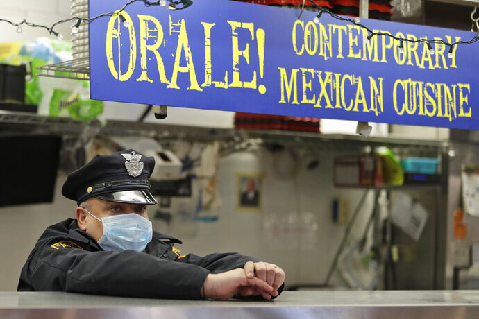 Patrolman Elliot Landrau keeps watch at the West Side Market, Friday, April 10, 2020, in Cleveland. There were fewer shoppers this year before the Easter holiday than in previous years due to the coronavirus. (AP Photo/Tony Dejak)