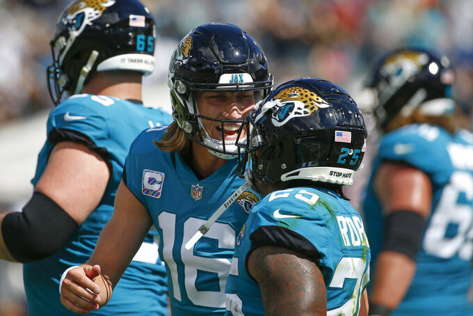Jacksonville Jaguars quarterback Trevor Lawrence (16) celebrates with running back James Robinson after Robinson ran a 1-yard touchdown against the Tennessee Titans during the first half of an NFL football game, Sunday, Oct. 10, 2021, in Jacksonville, Fla. (AP Photo/Stephen B. Morton)
