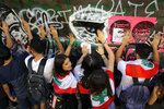 University students chant slogans as they beat their hands against a graffiti-covered wall during ongoing protests against the Lebanese government, in Beirut, Tuesday, Nov. 12, 2019. Protesters resumed demonstrations on Tuesday blocking some roads and governmental institutions. (AP Photo/Bilal Hussein)