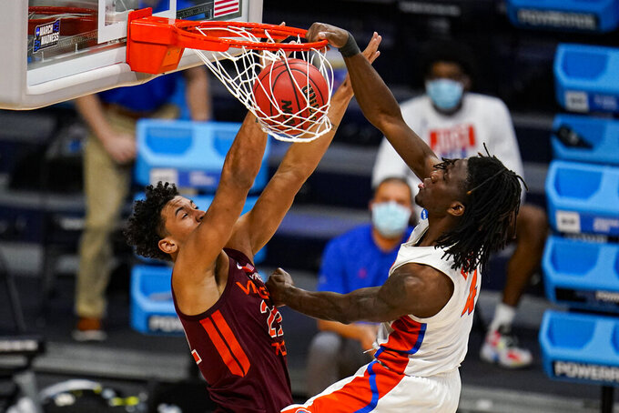 Florida forward Anthony Duruji (4) gets a dunk over Virginia Tech forward Keve Aluma (22) in overtime of a first round game in the NCAA men's college basketball tournament at Hinkle Fieldhouse in Indianapolis, Friday, March 19, 2021. Florida defeated Virginia Tech Hokies 75-70. (AP Photo/Michael Conroy)