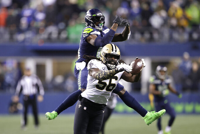 New Orleans Saints' Demario Davis (56) breaks up a pass intended for Seattle Seahawks' DK Metcalf in the final minute of the second half of an NFL football game, Monday, Oct. 25, 2021, in Seattle. (AP Photo/John Froschauer)