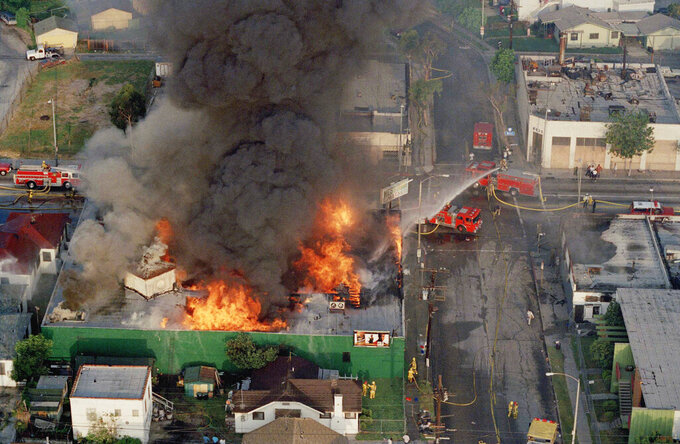 FILE - In this April 30, 1992 file photo, a fire burns out of control at the corner of 67th Street and West Boulevard in South Central Los Angeles. On April 29, 1992, four white police officers were declared innocent in the beating of black motorist Rodney King, and Los Angeles erupted in deadly riots. Three days later, 55 people were dead and more than 2,000 injured. Fires and looting had destroyed $1 billion worth of property. (AP Photo/Paul Sakuma)