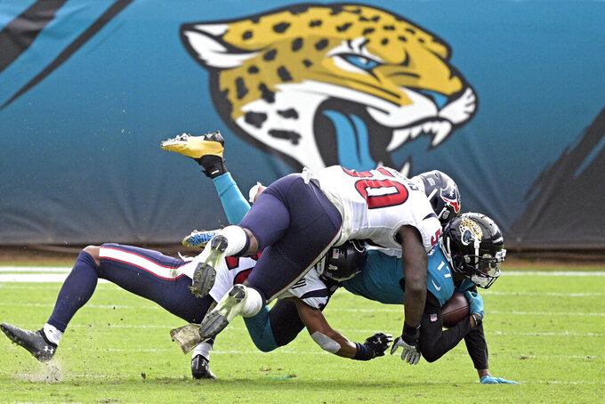Jacksonville Jaguars wide receiver DJ Chark Jr., right, is stopped by Houston Texans linebacker Tyrell Adams, top, and safety Jonathan Owens, left, during the second half of an NFL football game, Sunday, Nov. 8, 2020, in Jacksonville, Fla. (AP Photo/Phelan M. Ebenhack)