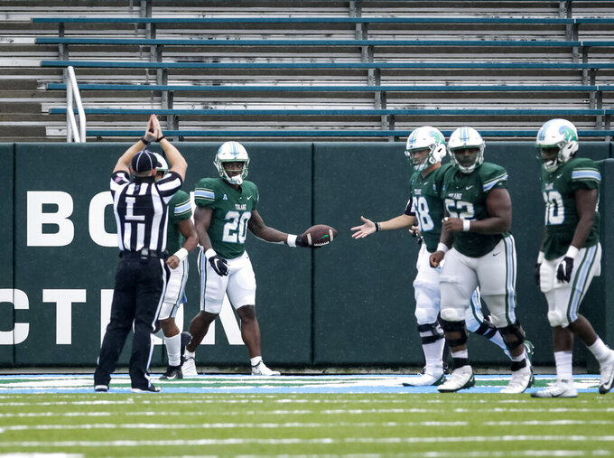 Tulane running back Cameron Carroll (20) hands the ball to a referee after being tackled in the end zone by Navy for a safety during the second half of an NCAA college football game, Saturday, Sept. 19, 2020, in New Orleans. (Scott Threlkeld/The Times-Picayune/The New Orleans Advocate)