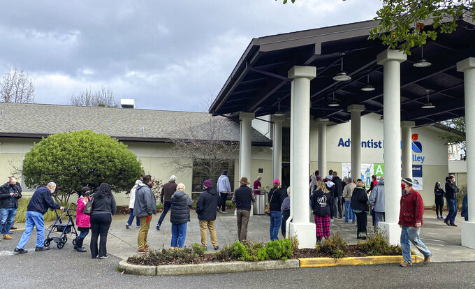 In this photo provided by The Mendocino Voice, people line up outside the Adventist Health Ukiah Valley Medical Center, Monday, Jan. 4, 2021, in Ukiah, Calif., to get the Moderna COVID-19 vaccination during an emergency vaccine drive. A power failure for the freezer holding the county's ration of the Moderna vaccines forced the emergency distribution of 850 doses of that vaccine. (Jethro Bowers/The Mendocino Voice via AP)