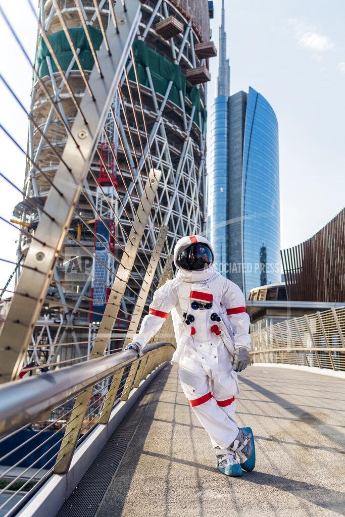 Male astronaut standing on one leg at bridge