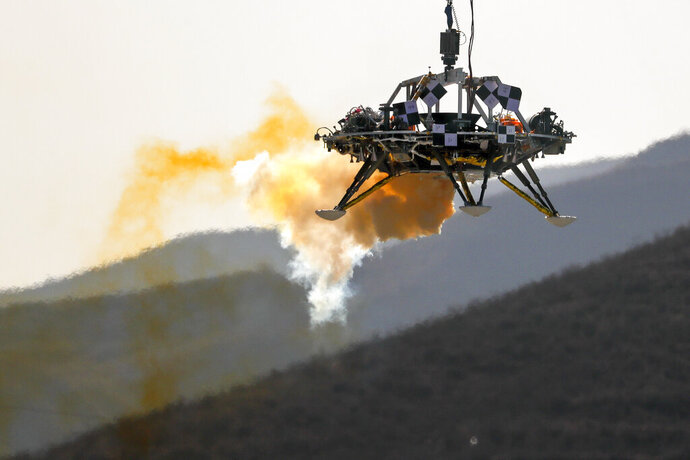 A lander is lifted during a test of hovering, obstacle avoidance and deceleration capabilities at a facility in Huailai in China's Hebei province, Thursday, Nov. 14, 2019. China has invited international observers to the test of its Mars lander as it pushes for inclusion in more global space projects. Thursday's test was conducted at a site outside Beijing simulating conditions on the Red Planet, where the pull of gravity is about one-third that of Earth. (AP Photo/Andy Wong)