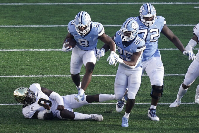 North Carolina running back Michael Carter (8) jumps over Wake Forest linebacker Ja'Cquez Williams (8) defended by North Carolina running back Javonte Williams (25) during the second half of an NCAA college football game in Chapel Hill, N.C., Saturday, Nov. 14, 2020. (AP Photo/Gerry Broome)