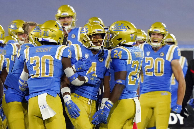 UCLA defensive back Stephan Blaylock (4) is congratulated by teammates after he intercepted an Arizona pass during the second half of an NCAA college football game Saturday, Nov. 28, 2020, in Pasadena, Calif. (AP Photo/Marcio Jose Sanchez)