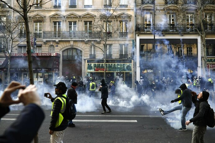 Teargas is used to disperse demonstrators during minor clashes with police in Paris, Saturday, March 23, 2019. The French government vowed to strengthen security as yellow vest protesters stage a 19th round of demonstrations, in an effort to avoid a repeat of last week's riots in Paris. (AP Photo/Kamil Zihnioglu)