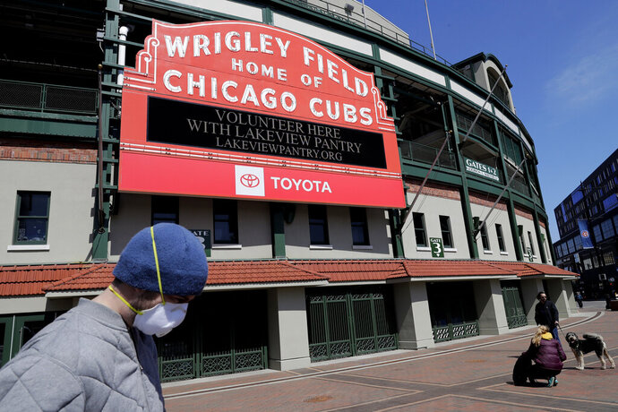 FILE - In this April 16, 2020 file photo, Wrigley Field's marquee displays Lakeview Pantry volunteer information in Chicago. The Chicago Cubs are instituting pay cuts because of the coronavirus crisis, but there will be no furloughs through the end of June. A person with direct knowledge of the situation says the pay cuts were based on compensation. President of baseball operations Theo Epstein and president of business operations Crane Kenney took the highest reductions. The person, who spoke to The Associated Press on Thursday, May 21, 2020 on condition of anonymity because of the sensitivity of the situation, says 80% of associates are taking a pay cut of 20% or less.  (AP Photo/Nam Y. Huh, File)