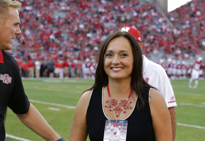 FILE - In this Sept. 2, 2017, file photo, Wendy Anderson, center, wife of Arkansas State head coach Blake Anderson, obscured at left, smiles after chatting with Nebraska head coach Mike Riley, rear, before an NCAA college football game in Lincoln, Neb. Wendy Anderson has died after a two-year fight with breast cancer. Blake Anderson says his wife died Monday night, Aug. 19, 2019,  just hours after the school announced he would be taking a leave of absence. He said on Twitter :