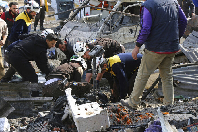 This photo provided by the Syrian Civil Defense White Helmets, which has been authenticated based on its contents and other AP reporting, shows members of the Syrian Civil Defense transporting an injured person after an airstrike hit the northern town of Maaret al-Numan, in Idlib province, Syria, Monday, Dec. 2, 2019. Syrian opposition activists say the airstrike on the market in Maaret al-Numan, a rebel-held town in the country's northwest, has killed at least 10 civilians. (Syrian Civil Defense White Helmets via AP)