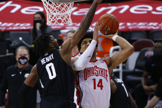 Ohio State's Justice Sueing, right, tries to shoot over Michigan State's Aaron Henry during the first half of an NCAA college basketball game Sunday, Jan. 31, 2021, in Columbus, Ohio. (AP Photo/Jay LaPrete)