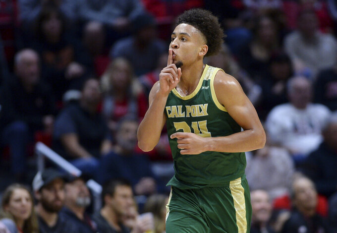 Cal Poly guard Junior Ballard gestures toward the crowd after a 3-point basket during the first half of the team's NCAA college basketball game against San Diego State on Saturday, Dec. 28, 2019, in San Diego. (AP Photo/Orlando Ramirez)