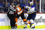 Philadelphia Flyers' James van Riemsdyk, center, is shoved into an official by St. Louis Blues' Robert Bortuzzo, right, during the first period of an NHL hockey game, Monday, Jan. 7, 2019, in Philadelphia. (AP Photo/Matt Slocum)