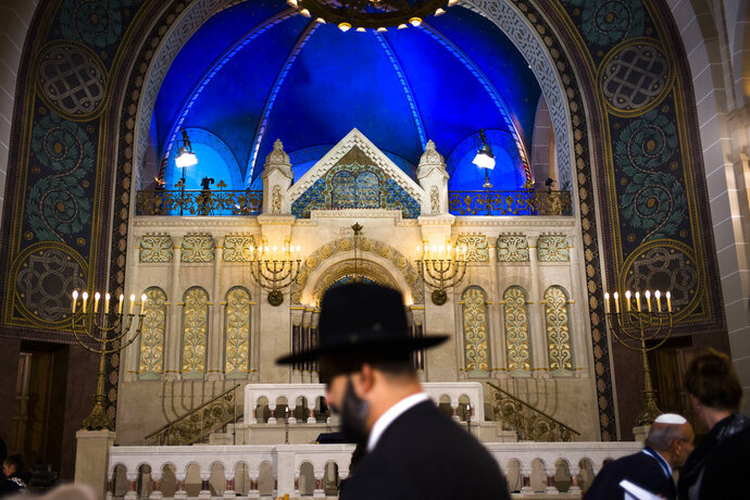 A rabbi arrives at the synagogue Rykestrasse in the district Prenzlauer Berg in Berlin, Friday, Nov. 9, 2018 to attend an event commemorating the Night of Broken Glass 1938, in which Nazis burned and vandalized synagogues and Jewish businesses across the country and killing over 400 people. (AP Photo/Markus Schreiber)