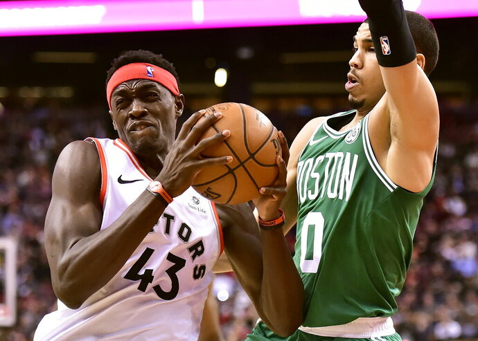 Toronto Raptors forward Pascal Siakam (43) drives into Boston Celtics forward Jayson Tatum (0) during second half NBA basketball action in Toronto on Tuesday, Feb. 26, 2019. (Frank Gunn/The Canadian Press via AP)