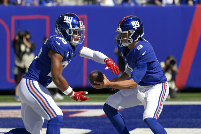 New York Giants quarterback Daniel Jones (8) hands the ball off to New York Giants running back Saquon Barkley, left, during the first half of an NFL football game, Sunday, Sept. 26, 2021, in East Rutherford, N.J. (AP Photo/Bill Kostroun)