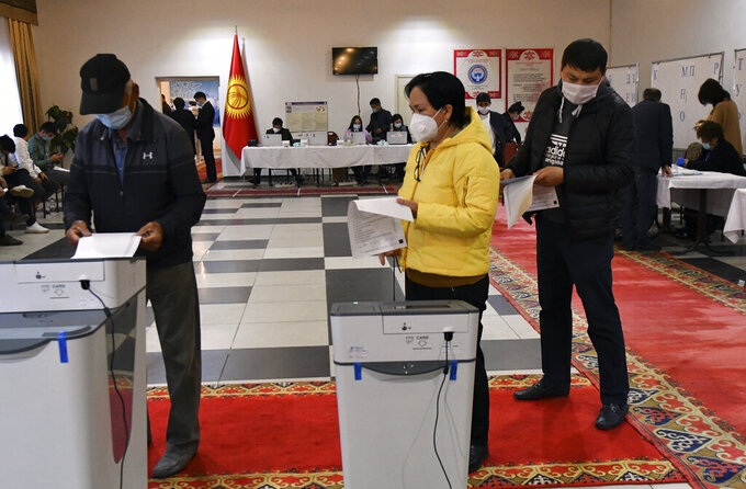 Voters cast their ballots at a polling station during the referendum in Bishkek, Kyrgyzstan, Sunday, April 11, 2021. Voters in Kyrgyzstan cast ballots Sunday on whether to approve a new constitution that would substantially increase the president's powers. The Sunday referendum comes three months after Sadyr Zhaparov was elected president, following the ouster of the previous president amid protests, the third time in 15 years that a leader of the Central Asian country had been driven from office in a popular uprising. (AP Photo/Vladimir Voronin)